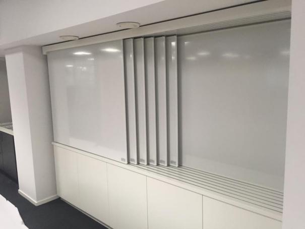 1. Whiteboard system anpassade efter vägg. Skåp under för förvaring. Total skrivyta 14,4 kvm på en total yta av endast tre meter.