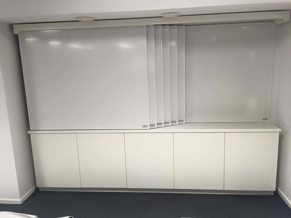 2. Whiteboard system anpassade efter vägg. Skåp under för förvaring. Total skrivyta 14,4 kvm på en yta av endast tre meter.